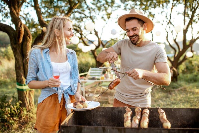 Couple having barbecue in the garden stock photo