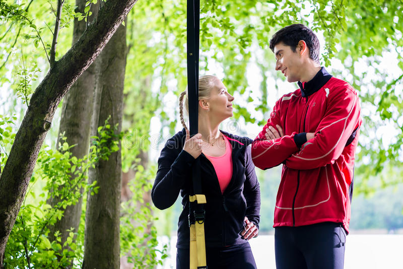 Couple having break from sling training royalty free stock photo