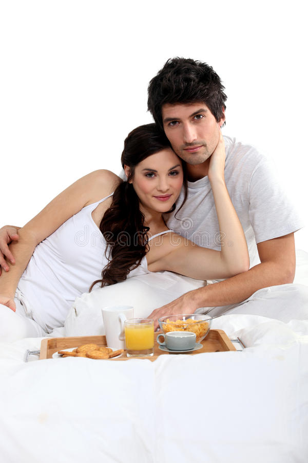 Couple having breakfast in bed royalty free stock photos