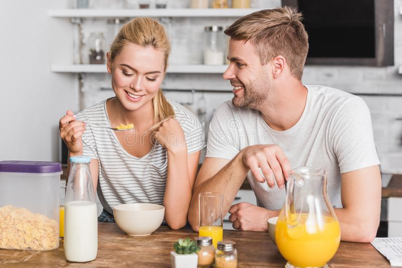 couple having breakfast and eating corn flakes with milk royalty free stock image