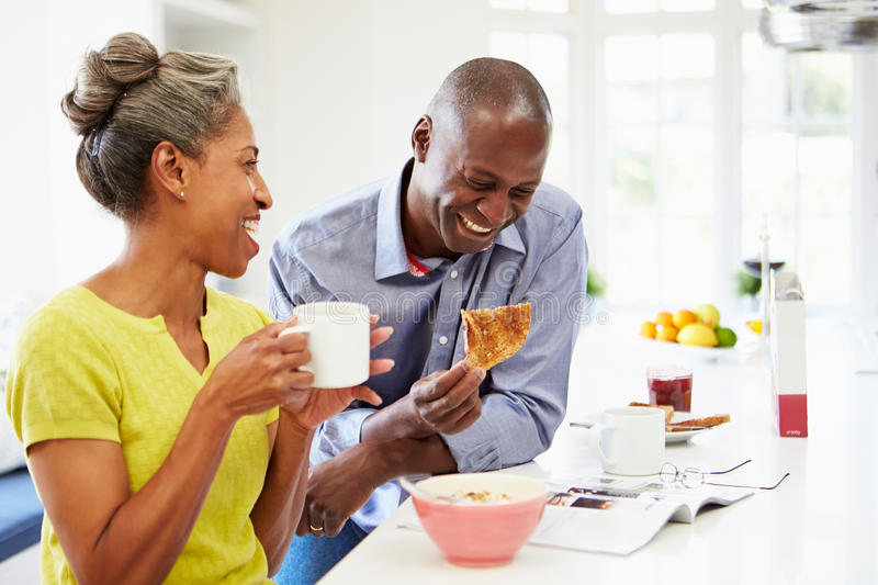Couple Having Breakfast And Reading Magazine In Kitchen. Sitting Down At Table royalty free stock photos