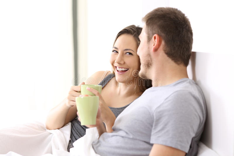 Couple having breakfast and talking on a bed. Happy couple having breakfast and talking on a bed of an hotel room or home royalty free stock image
