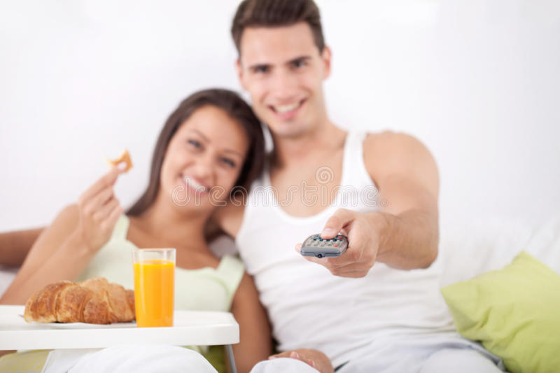 Couple Having Breakfast And Watching TV Royalty Free Stock Photography