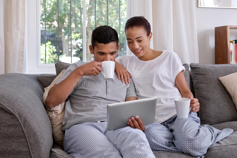Couple having coffee and looking at tablet royalty free stock photos