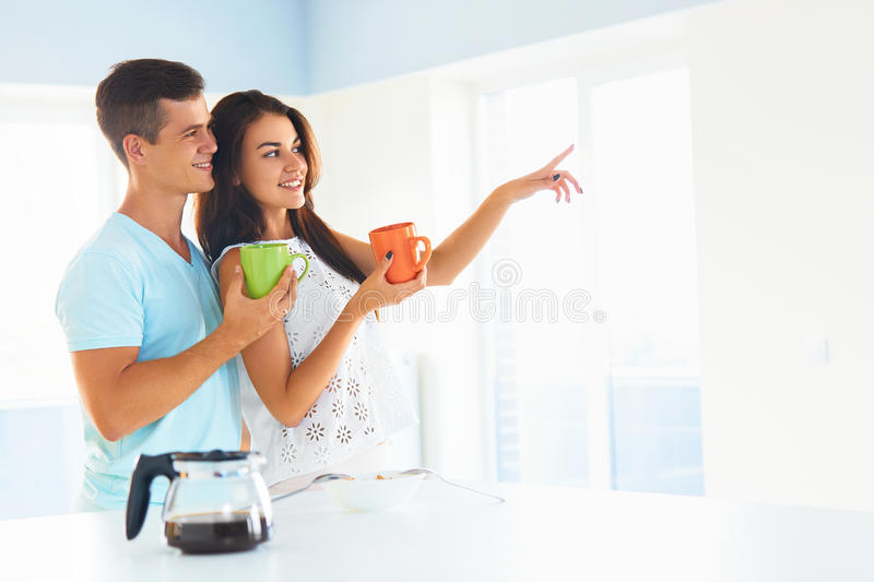Couple having conversation in the morning. Happy couple having conversation in the morning. Woman sitting on worktop and pointing her finger out the window, men royalty free stock photos