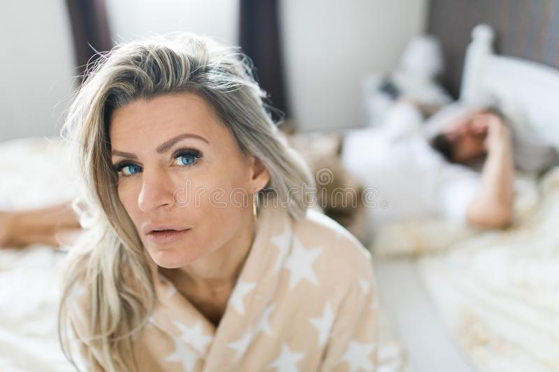 Couple having crisis in bed. Woman sitting on bed`s edge royalty free stock photos