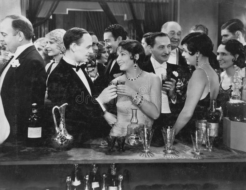 Couple having drink at crowded bar stock images