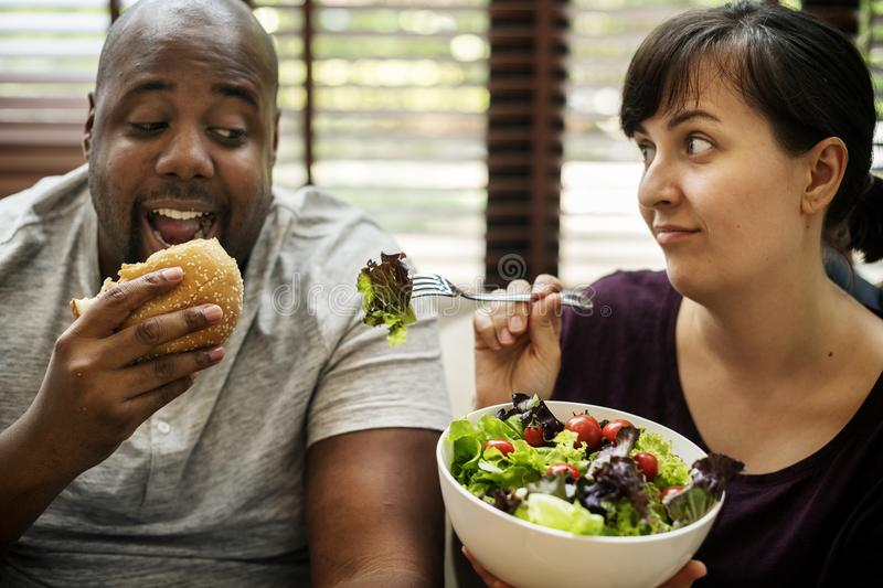 Couple having fast food on the couch royalty free stock images