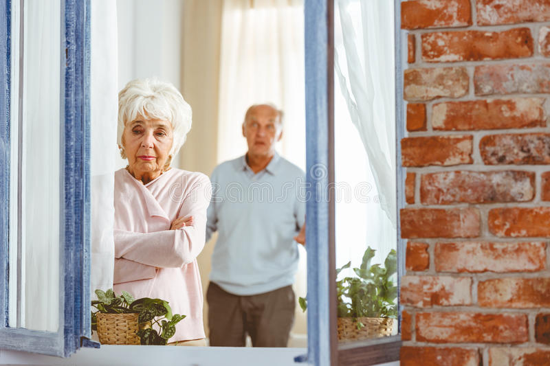 Couple having a fight. Couple of seniors having a fight in their apartment with open window royalty free stock image