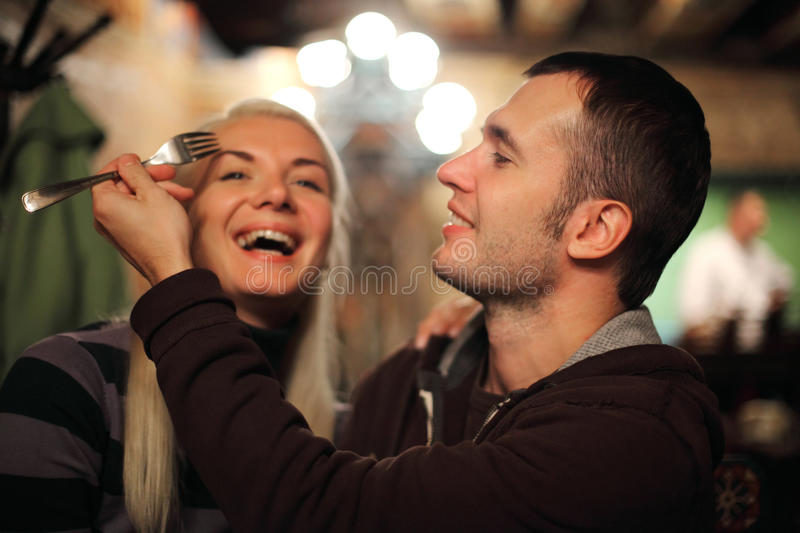 Couple having fun. Young couple having fun in restaurant royalty free stock images