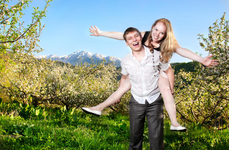 Couple having fun around bloomy trees. Beautiful couple smiling and having fun with each other around bloomy apple trees at mountain background royalty free stock photos