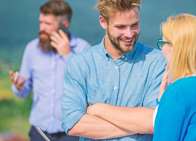 Couple having fun while busy businessman speak on phone. Couple flirting while man busy with mobile conversation. Couple having fun while busy businessman speak royalty free stock image