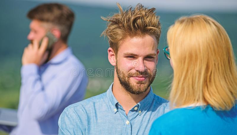Couple having fun while busy businessman speak on phone. Partners glad to see each other. Face to face conversation. Advantages concept. Couple happy flirting royalty free stock photography