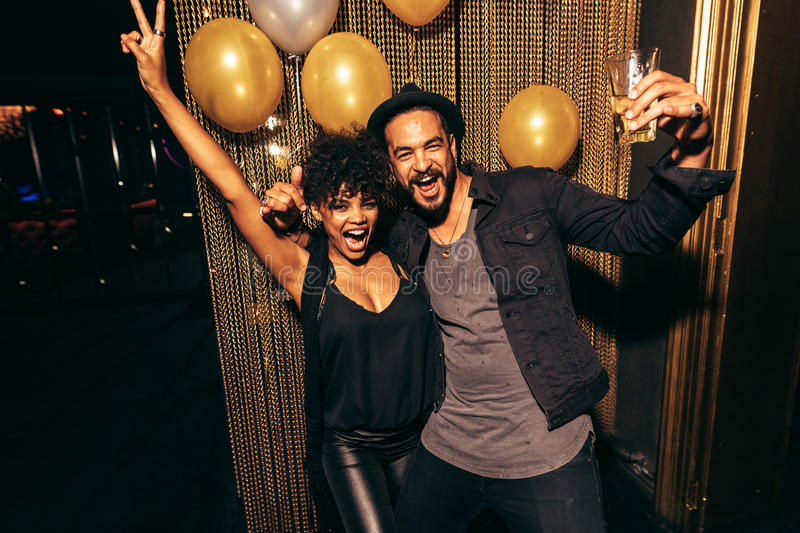 Couple having fun at disco party. Couple smiling and dancing, having fun during disco party. Happy men and women enjoying party at nightclub stock image