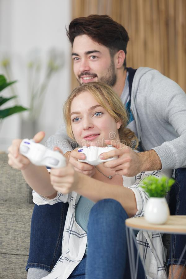 Couple having fun at home playing video games. Happy royalty free stock photo