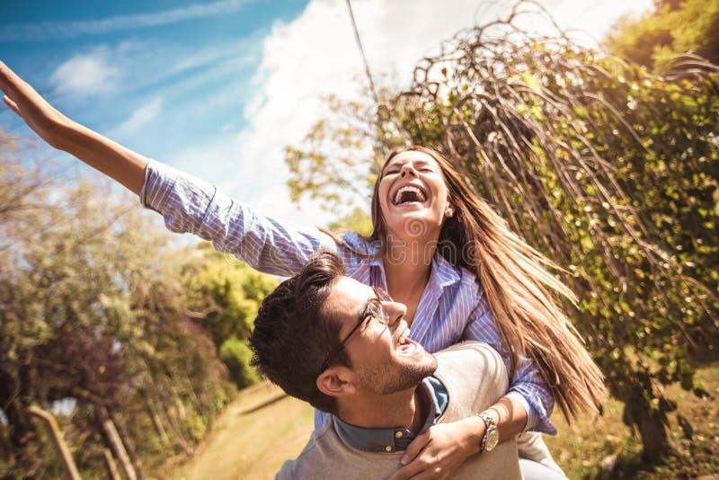 Couple having fun man giving piggyback to woman. Couple having fun men giving piggyback to women in park stock photos
