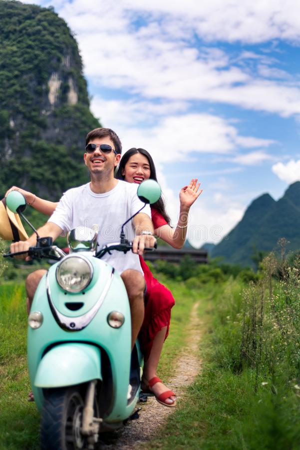 Couple having fun on motorbike around rice fields in China stock images
