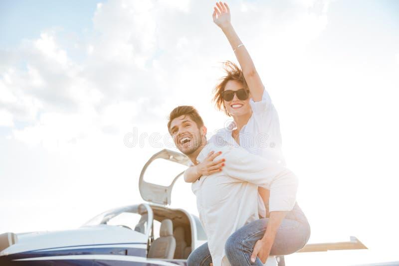Couple having fun on runway in airport. Happy young couple having fun on runway in airport royalty free stock photo