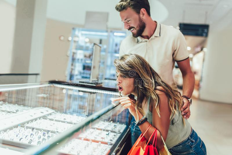 Couple having fun in shopping mall while doing shopping together. Young couple having fun in shopping mall while doing shopping together royalty free stock images