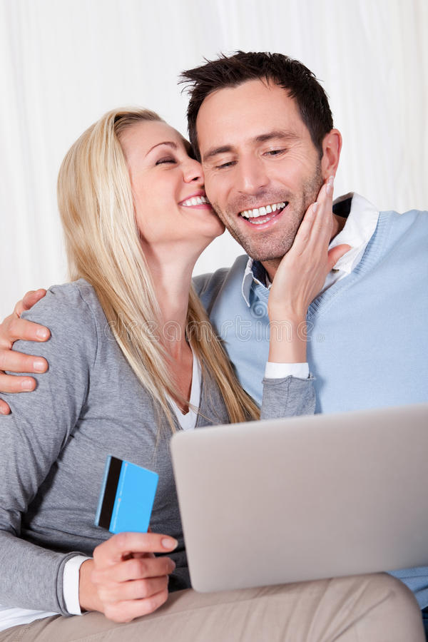 Couple having fun shopping online. Sitting laughing as they read the screen on their tablet stock photography