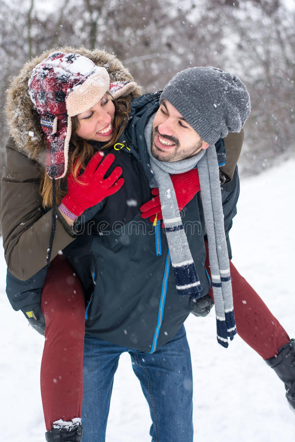 Couple having fun in snow covered park stock photo