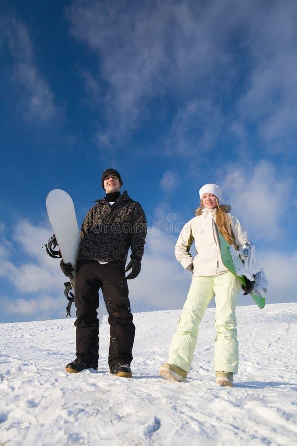 Couple having fun on snowboard stock image
