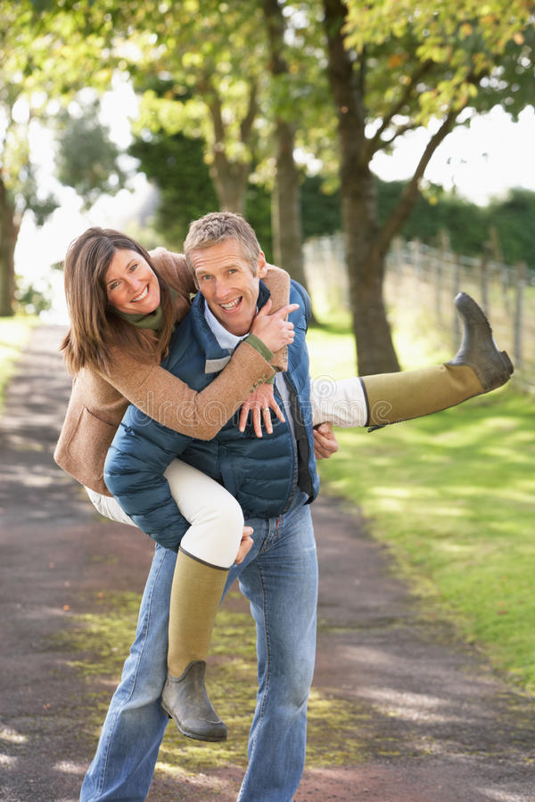 Couple Having Fun Whilst Walking In Park. Couple Having Fun Whilst Walking In Autumn Park stock photos