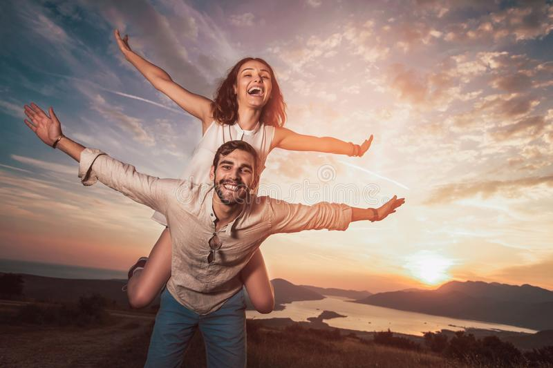 Couple having having fun in nature, behind them is a beautiful sunset over Boka Bay stock images