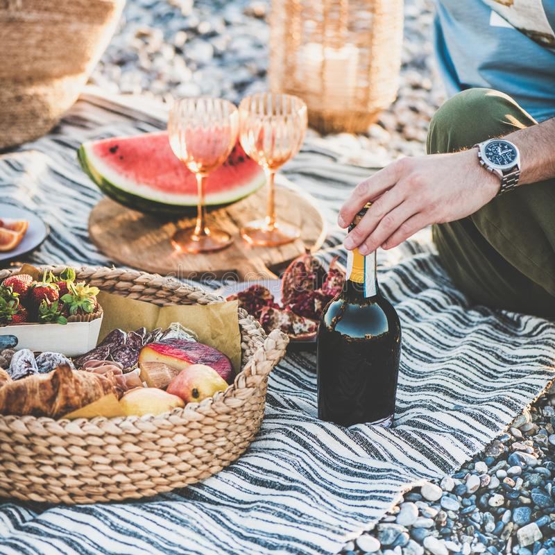 Couple having picnic with bottle of sparlking wine, square crop stock photos