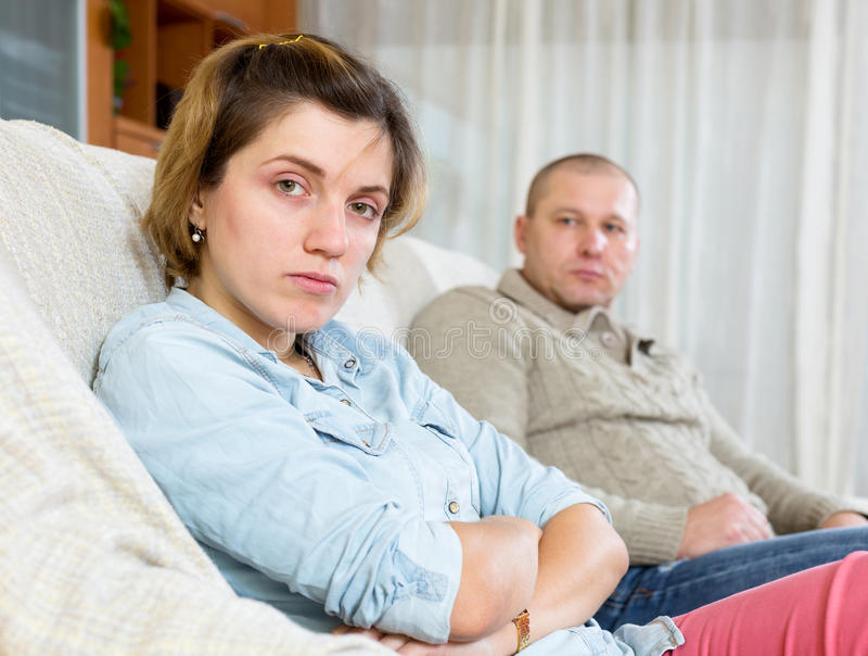 Couple having quarrel at home. Couple quarrel. Upset ordinary women against sadness men at home stock images