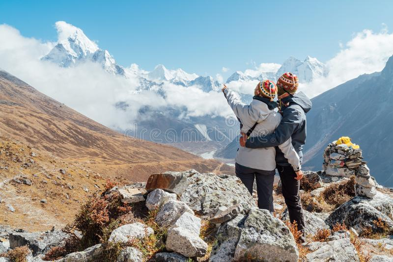 Couple having a rest on Everest Base Camp trekking route near Dughla 4620m. Backpackers left Backpacks, embracing and enjoying. Valley view with Ama Dablam stock images