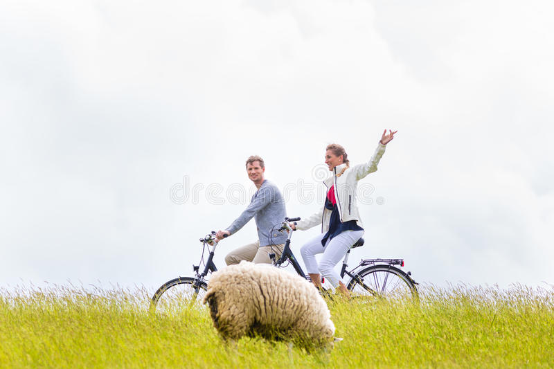 Couple having sea coast bicycle tour at levee royalty free stock photos
