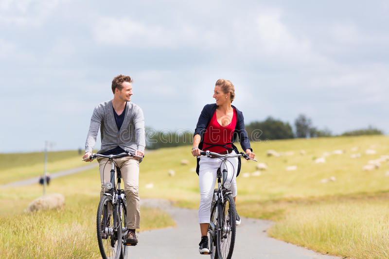 Couple having sea coast bicycle tour at levee royalty free stock images