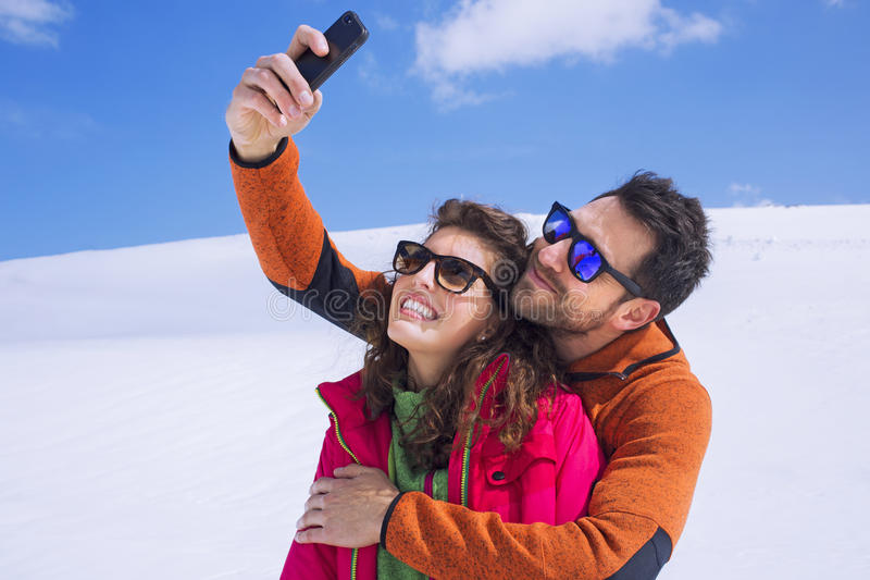 Couple having a selfie on the snow. In mountain stock image