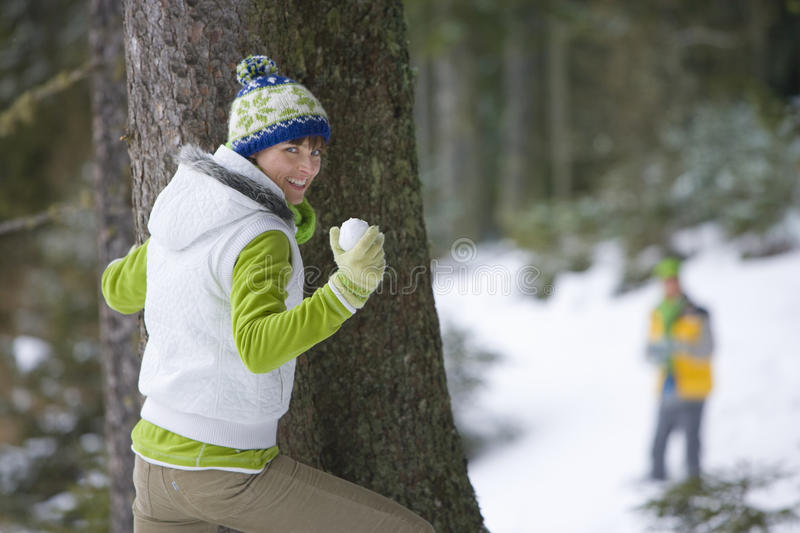 Couple having snowball fight together in woods royalty free stock photography