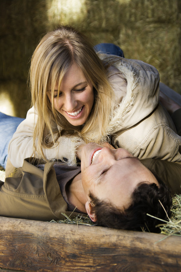 Couple in hay. Mid-adult Caucasian couple laughing and lying in hay royalty free stock images