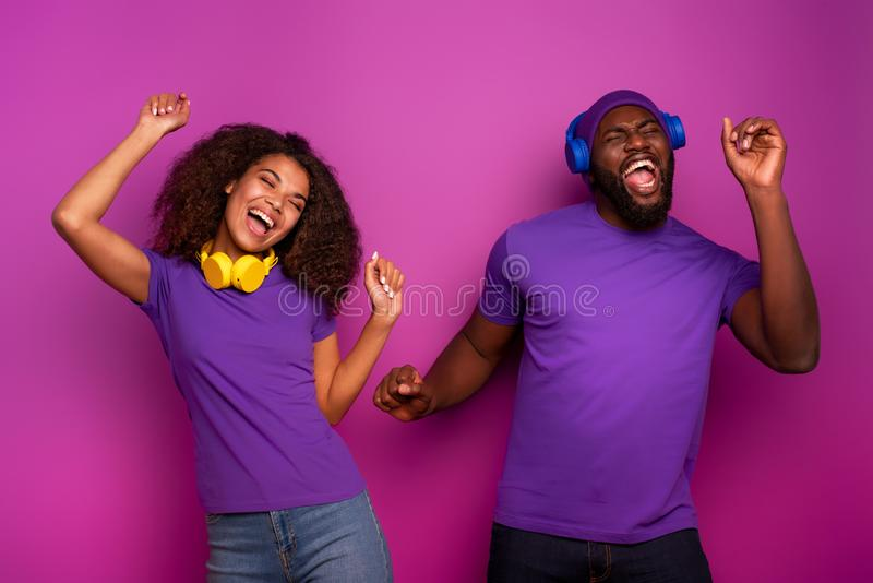 Couple with headset listen to music and dance with energy on violet background. Couple with headset listen to music and dance on violet background stock photos