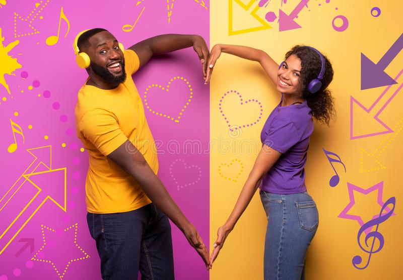 Couple with headset listen to music and make the shape of heart with arms. violet and yellow background. Colors stock image