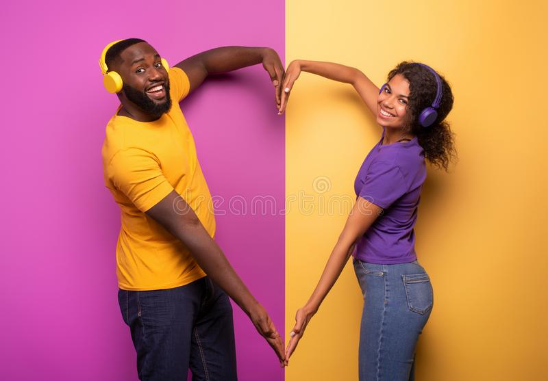 Couple with headset listen to music and make the shape of heart with arms. violet and yellow background. Colors stock photography