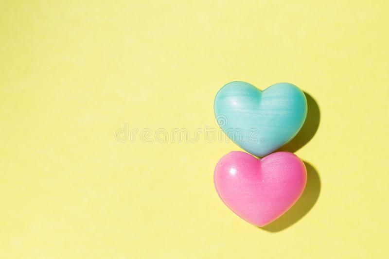 Couple of heart shapes over yellow table. Valentines day symbol stock images