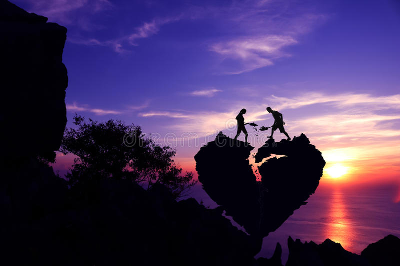 Couple helping to shoveling stone for repair the broken heart shape rock on the mountain. royalty free stock image
