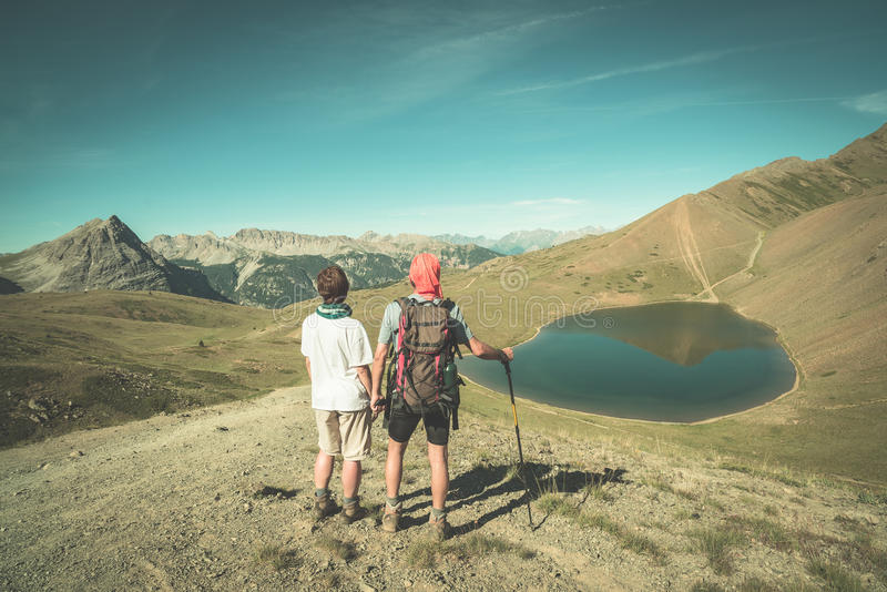 Couple of hiker on the mountain top looking at blue lake and mountain peaks. Summer adventures on the Alps. Wide angle view from a royalty free stock images