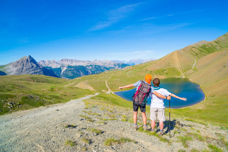 Couple of hiker on the mountain top looking at blue lake and mountain peaks. Summer adventures on the Alps. Wide angle view from a. Bove stock photo