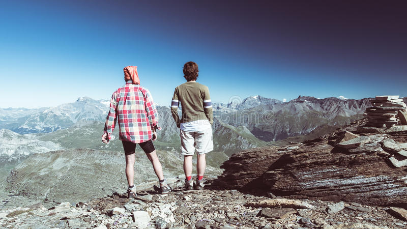 Couple of hiker on the mountain top looking at expasnive view and mountain peaks. Summer adventures on the Alps. Wide angle view f royalty free stock photo