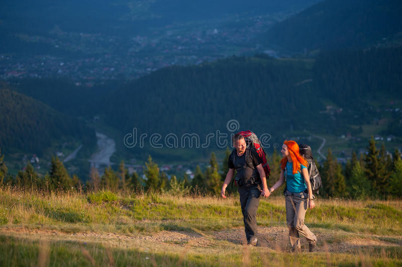 Couple hikers with backpacks holding hands, walking in the mountains royalty free stock photos