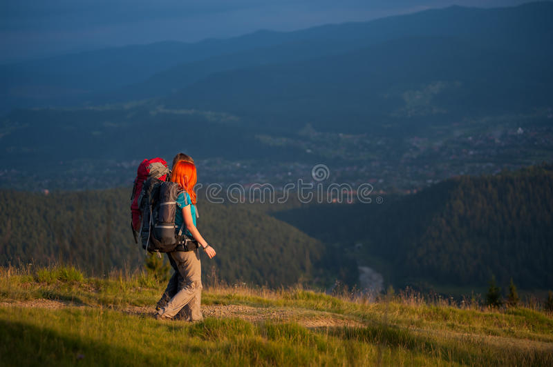 Couple hikers with backpacks holding hands, walking in the mountains royalty free stock photography
