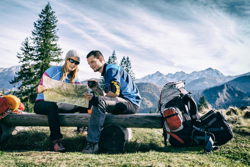 Couple hikers with map in mountains. Man and women hikers hiking in mountains. Young couple camping, looking at map and planning trip or get lost. Getting rest royalty free stock images