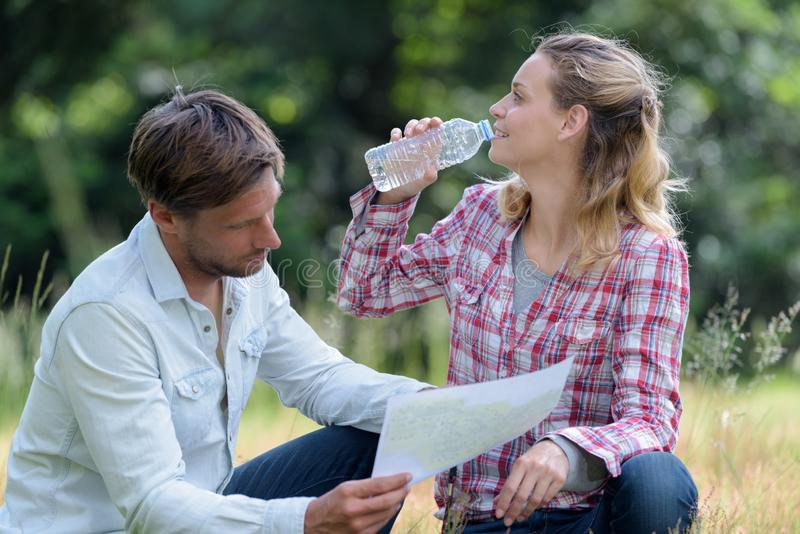 Couple hikers resting in forest drinking water royalty free stock photo