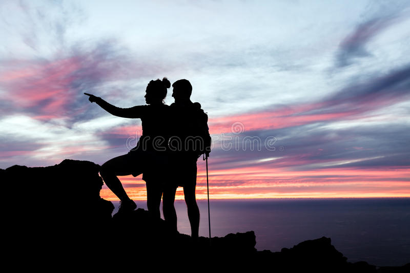 Couple hikers silhouette in mountains. Man and women hiking silhouette in mountains, sunset and ocean. Male and female couple hikers with walking sticks on top royalty free stock photography