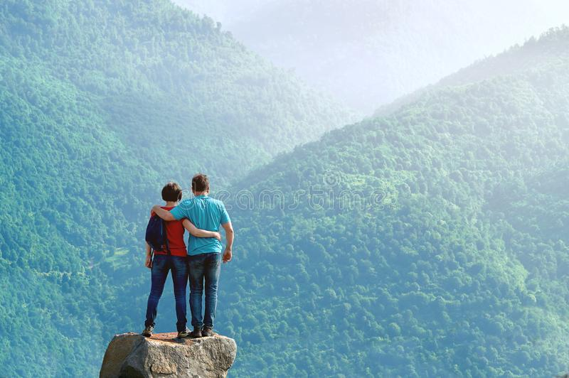 Couple of hikers standing embraced on the cliff edge and enjoying beautiful morning view in the mountains. In Armenia stock photography